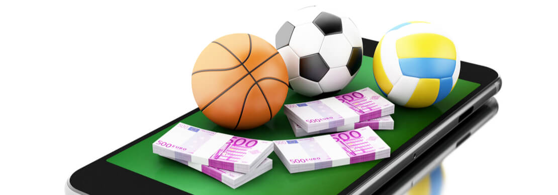a mobile phone with soccer ball, basketball and cash sitting on it